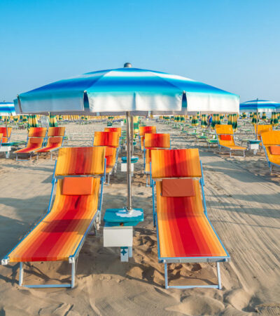 Blue umbrellas and chaise lounges on the beach of Rimini in Italy